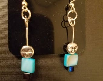 A moon face over a sky blue bead on Silver wire