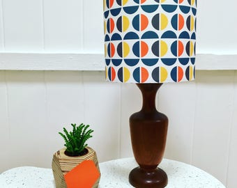 Handmade drum lampshade made using exclusively designed fabric with repeated semi circle geometric pattern in orange, mustard, grey and teal