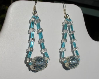 Blue seed beads earrings with a focal glass bead in a transparent blue hue.The beads are strung on a strong silky thread.