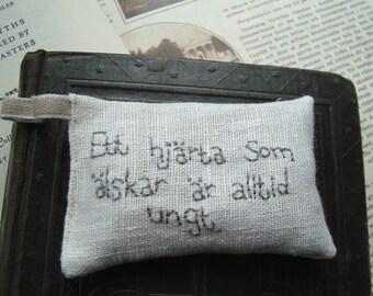 Lavender sachet in linen with Swedish embroidered text 'Ett hjärta som älskar är alltid ungt'