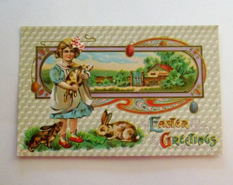 Antique Easter postcard P. Sanders Edwardian girl with bunnies and house in background