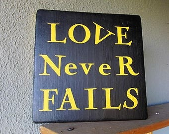 """Custom Wood Sign Says, """"Love Never Fails""""    Yellow on Ink Black Paint, Beautiful Inspirational Wood Sign , Looks Good, Great as a  Gift!"""