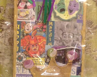 Mardi Gras is for everyone mixed media collage on canvas displayed on a wooden easel.
