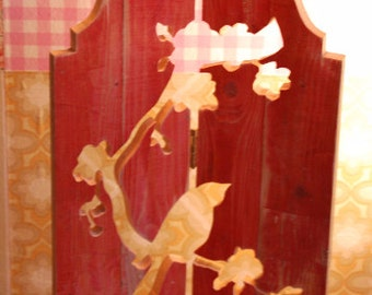 Wooden window decoration with a bird on a twig with blossom
