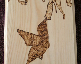 Woodburned hummingbird taking nectar from a flower