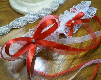 Wedding garter in white lace and topped with Red satin ribbon bows