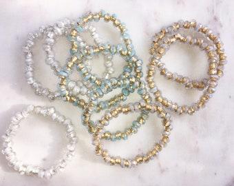 stackable bracelets . gold, aqua, frosty white, silver, stretch cord . 1 bracelet