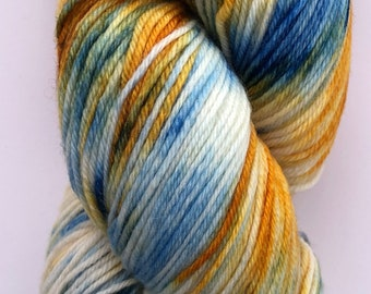 A beautiful, soft, hand dyed yarn in shades of blue, orange, yellow and white.