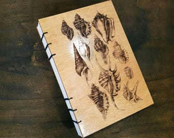 Notebook with shells engraved on wooden cover. Bound with Coptic Stitching.
