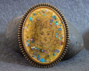 Resin brooch with etherial face, marbling and shimmer