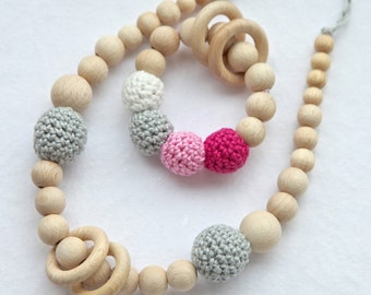 Set of 2. Grey nursing rings necklace and pink, grey and white teething ring toy.