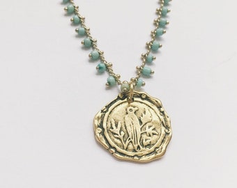 Syllo Necklace — vintage-look, antique style, gold wax envelope seal BIRD charm, blue seed-bead detail, turquoise stones at clasp boho gypsy