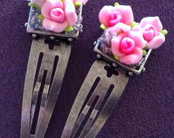 Two pink rosette hair clips.