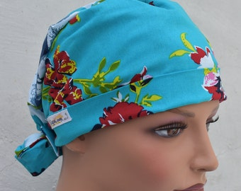 Tie Back Scrub Cap scrub hat featuring a blue material with flowers in red white blue and green