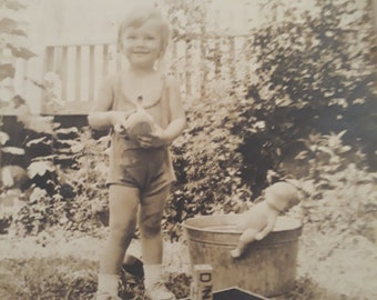 Sweet smiling girl dressed in romper holding a toy duck giving babydoll a bath outdoors in galvanized metal tub with toys in grass 1935