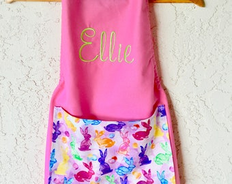 Girls personalized apron includes name in pink with large pocket.