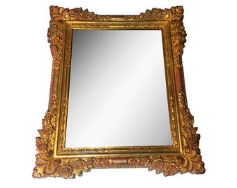 Large vintage ornate hand carved solid wood mirror with gold paint and red highlights.