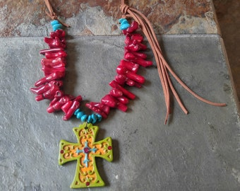 Cross pendant, with turquoise and red stones. Suede fringe.