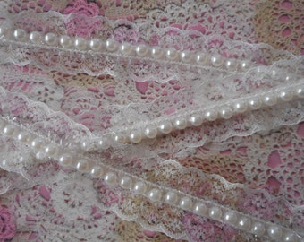 Fine off-white lace, polyester, floral design, band of ivory pearls, 4.00 cm wide, sold by the yard.