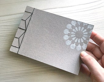 HANDMADE NOTEBOOK A6, Japanese stab-binding with black cotton, 40 white blank pages, textured craft card cover, white daisy stencil pattern