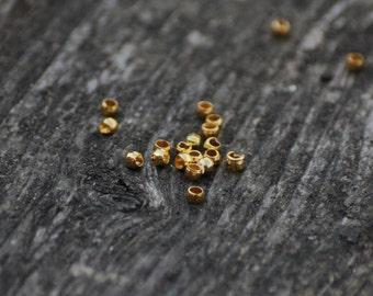 50 tiny brass crimp beads 2 mm - golden color