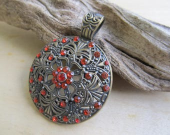 Filigree large pendant round shape 61 x 47 x 4 mm bronze metal and Ruby Red rhinestones.