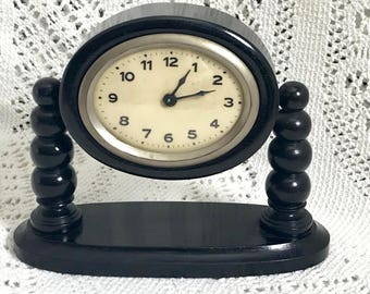 Antique Art Deco Ebony Mantel Clock Black Wood. Oval Face in Tilting Casing on Turned Arm Supports. Oval Base Early 1900s Windup NOT working