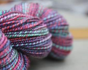Sport weight superwash wool and tencel yarn, dyed and hand spun.