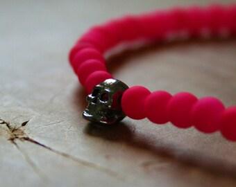 Neon Skull: an elastic beaded bracelet with gunmetal skull and matte neon pink glass beads.