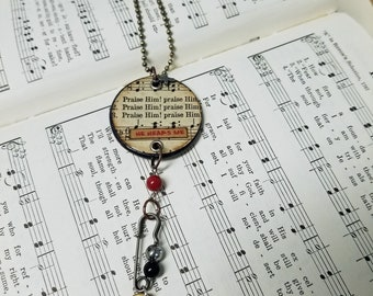 Heartsongs - Praise Him, Praise Him is an altered wood poker chip with paper hymn snippets, metal findings and charms