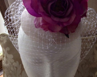 Elegant white coloured fascinator with 3 purple flowers and white netting!