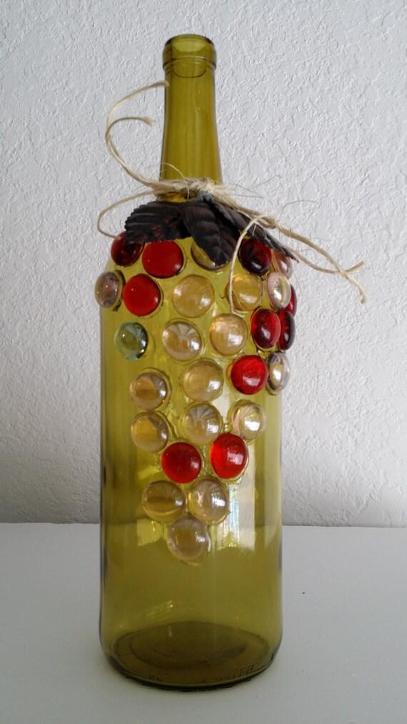 Botella de vino decorada con un racimo de uva en joyas