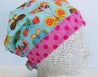 Tie Back Scrub Cap scrub hat featuring a blue material with butterflies in pink blue yellow green and orange with a coordinating band 2t