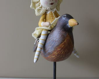 Whimsical art doll riding a Robyn