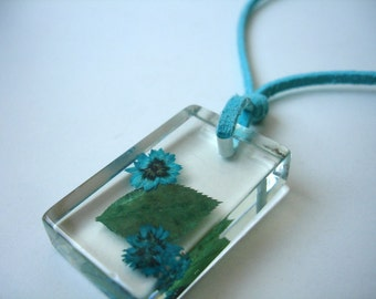 Resin pendant with real flowers and a leaf on a aqua cord