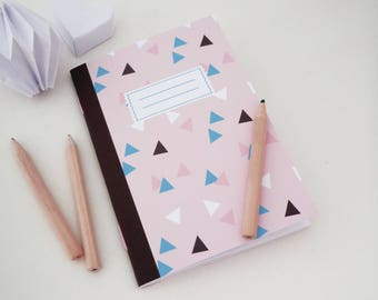A6 notebook illustrated with pink, black and blue triangles