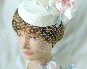 Wedding  hat-veil with flowers of silk and a bouquet on a dress