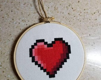 8-bit pixel heart cross stitch completed and framed.