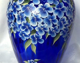 """Hand painted cobalt blue vase with blue flowers and sage green leaves, measures 13"""" tall and 9"""" wide at widest point."""