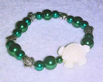 Two-tone green glass with stone and silver turtles.