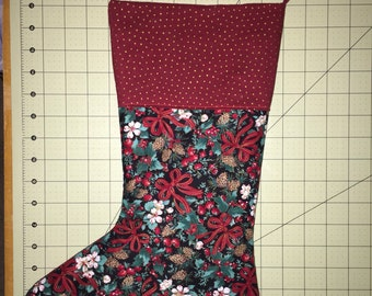 Christmas stocking, pine cones and red ribbons