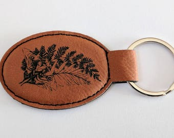 TLOU Ellie's Tattoo Keychain, laser engraved on brown leatherette, oval. Customise with your name or any other inscription!