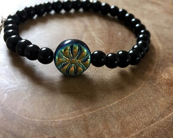 Doublesided: an elastic beaded bracelet with black glass beads and a Czech glass bead with a black and irisdesant side. Gold, green, blue