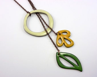 Handmade enameled adjustable lariat necklace; creamy ivory circle with yellow flower and green leaf dangles