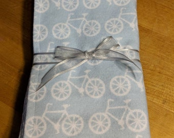 Set of four soft flannel burp cloths in blue bicycle print
