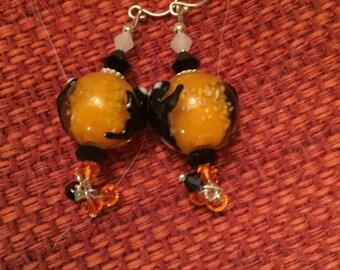 Orange lampwork earrings with black ghouls