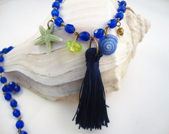 Long layering bright blue rosary style chain with navy tassel, sea shell and starfish charms, very beachy