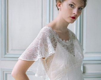 Vintage inspired  lace wedding dress sample with flutter sleeve, low V back, flowing skirt and  short train.