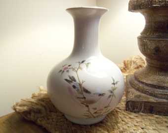 Vase with bird on cherry blossom branch