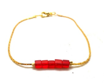 Gold minimalist bracelet, red square beads charms and co.